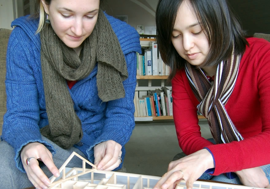 Two interns building an architectural model